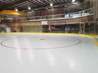 We traveled to Kapolei, Hawaii and inside to resurface two inline skate hockey rinks with Versacourt Speed Indoor tile. This is a picture of one end of the finished first court, showing all of one of the zone circles.