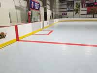 We traveled to Kapolei, Hawaii and inside to resurface two inline skate hockey rinks with Versacourt Speed Indoor tile. This is a finished view showing part of the center line and along one side.