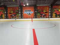 We traveled to Kapolei, Hawaii and inside to resurface two inline skate hockey rinks with Versacourt Speed Indoor tile. This shows much of the center line and the faceoff circle on the finished rink.