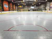 We traveled to Kapolei, Hawaii and inside to resurface two inline skate hockey rinks with Versacourt Speed Indoor tile. This is a view of the length of the completed, lined inline hocke and skating rink surface, from behind one of the goal lines.