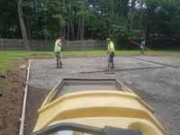 Emerald green and rust red home basketball court in Lynnfield, MA, featuring custom Celtics logo. Shown here spreading and smoothing cement being poured for a durable concrete court base.