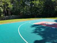 Emerald green and rust red home basketball court in Lynnfield, MA, featuring custom Celtics logo.
