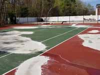 Decrepit tennis court in Manchester, NH repurposed and freshly surfaced as a basketball court in blue and red. Complete except paint over the exposed old surfaces around the new court. Shown here the old court surfaced after cleaning, patching and smoothing tp prepare for the new surface.