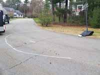 Home basketball court in Medway, MA, featuring royal blue and yellow Versacourt outdoor sport surface tiles. This is a view of the makeshift street court that the new installation replaces.