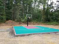 Green and red residential basketball court in Middleborough, MA.