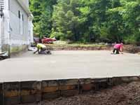 Milton, MA basketball court in a side yard, fit flush against a garage, featuring red and graphite Versacourt tiles. This picture shows the form and wet cement getting finishing touched before it turns to concrete.