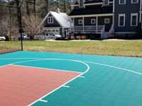 Residential basketball court in Norwell, MA, including goal system, mesh fencing, and an emerald green and rust red tile sport surface. Some trees and stumps were removed to make room in the yard and provide easy work access.