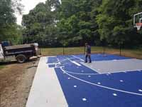 Backyard basketball court in village of Oakdale, Connecticut, in the historic town of Montville. Blue and silver surface with a custom logo that says Center Court with an orange basketball in place of the letter o.