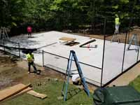 Residential backyard basketball court on fresh concrete base in stalled in Pepperell, MA, featuring fencing and an emerald green, titanium, and rust red sport tile surface. Shown here with the concrete base cured and the fence being installed.
