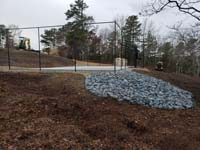 Multicourt for pickleball and basketball, fenced on three sides, on a hillside backyard in Plymouth, MA. View from the end opposite the gate, showing concrete base ready to have the tiles installed from the pallet in background.