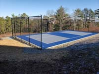 Hillside court primarily for pickleball, accessorized with a basketball goal and fencing, in Plymouth, MA. A look at the completed blue and grey court, in which adjacent stones for drainage are also visible.