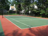 Restoration and resurfacing of large tennis court into multicourt with pickleball, hopscotch and shuffleboard for a condo complex in Duxbury, Massachusetts. Cracked old court before work began.