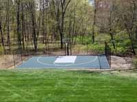 Backyard basketball court, in Versacourt slate green and titanium, in Stow, MA. This is a similar view of the finished court compared to the base preparation in the adjacent picture.