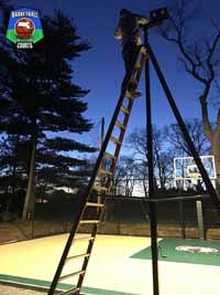 Bob adjusting optional lighting installed with outdoor basketball court in Swampscott, MA.