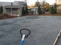 Photo from installation of a sand and emerald green residential backyard basketball court in Swampscott, MA. A better underlay makes a better, longer lasting base. Doing it right with hard packed crushed stone.