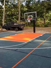 Graphite and orange home basketball court before fence installation in Walpole, MA.