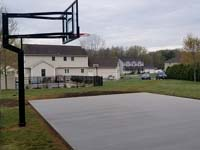 Completed reinforced concrete base, shown with hoop already installed, for green and grey backyard basketball court installation in Agawam, MA.