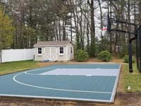Dark green and grey backyard basketball court in Agawam, MA.
