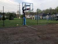 Already-installed hoop overlooking form and reinforcement for the concrete base for a dark green and grey backyard basketball court in Agawam, MA.