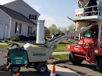 Background on the magic being done for basketball surface in Agawam, MA. Using a cart to drive small loads of cement to pour the court base, rather than heavy truck driving on lawn.