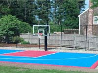 Light blue and red backyard basketball court, hoop and rebound fence in Halifax, MA.