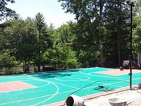 Backyard basketball court in Pembroke, MA, green and red with volleyball and lighting options.