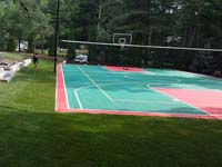 Backyard basketball surface, hoops, lights, and rebound fence in Pembroke, MA.