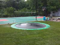 We installed the in-ground trampoline in the foreground, along with the green and red background court for various sports in Pembroke, MA.