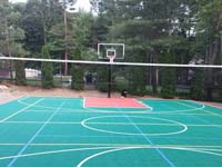 Commercial size multicourt, centered on basketball but with net and lines for volleyball and tennis, installed in a residential backyard in Pembroke, MA, along with an in-ground trampoline and lighting system for night play.