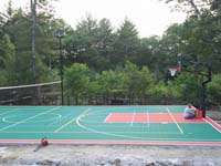 Professional installation in progress on a large backyard basketball court in Pembroke, MA, including accessories like a mid-court tennis and volleyball net with adjustable height, and lights for night games.