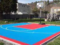 Backyard basketball court in Beverly, MA, using light blue and red outdoor tiles.