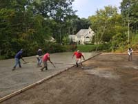 cement being poured and worked into one half of the base form for what will become a large emerald green and titanium backyard basketball court in Bolton, MA.