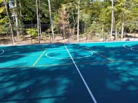 View of center court and secondary game lines on large emerald green and titanium backyard basketball court in Bolton, MA.
