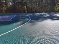 Surface between end and center court areas of large emerald green and titanium backyard basketball court in Bolton, MA.