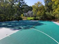Long view of bulk of large emerald green and titanium backyard basketball court in Bolton, MA, with orange secondary sport lines visible in center court area.