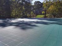 Sun drenched view down part of large emerald green and titanium court in Bolton, MA, showing relative close-up of the tiles that make up the ergonomic, high performance surface.