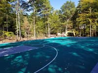 Long view at an angle of most of large emerald green and titanium backyard basketball court in Bolton, MA.