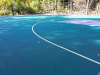 Closer view of tile surface of part of large emerald green and titanium backyard basketball court in Bolton, MA, showing off hoop system and containment fence.