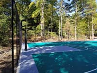 View of hoop end of large emerald green and titanium backyard basketball court in Bolton, MA, with emphasis on the goal system and optional fencing.