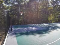 Sunny side view of goal end of large emerald green and titanium backyard basketball court in Bolton, MA.