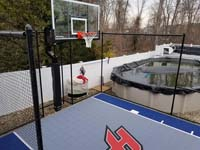 Former small, unused space in back yard by above ground pool became the home of a small blue and grey basketball court in Braintree, MA.