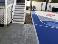 Small blue and grey basketball court with custom red H logo by existing pool in Braintree, MA, looking toward hoop end and featuring associated new patio by deck and bulkhead.