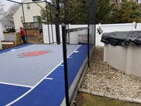 Small blue and grey backyard basketball court by pool in Braintree, MA.