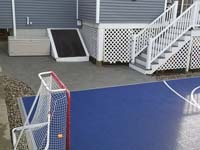 Small blue and grey basketball court in Braintree, MA, showing corner detail, associated hardscapes, and hockey net.