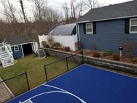 Context and detail of blue and grey small backyard basketball court with custom red H logo in Braintree, MA.