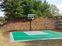 Green personal basketball court in Bridgewater, MA.