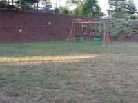 Future site of green and silver backyard basketball court in Bridgewater, MA.