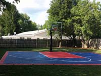 Small navy blue and red backyard basketball sport surface in Canton, MA.