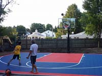 Dad watches kid shoot a hoop, ball in midair, on newly installed backyard basketball court in Canton, MA.