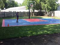 Kids on completed blue and red residential basketball court in Canton, MA, watering the new grass surrounding it.